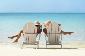two women relaxing in adirondack chairs on a tropical beach